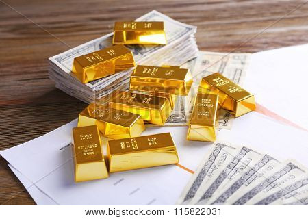 Gold bars with dollar banknotes on paper background