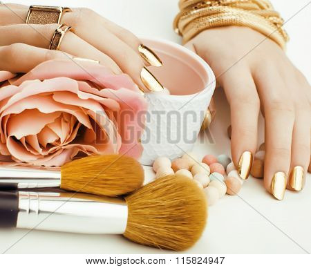 woman hands with golden manicure and many rings holding brushes, makeup artist stuff stylish, pure c