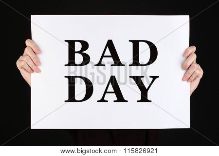 Woman holding poster with text Bad Day in front of her face isolated on black