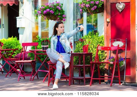 Young woman taking self portrait at outdoor cafe in european city