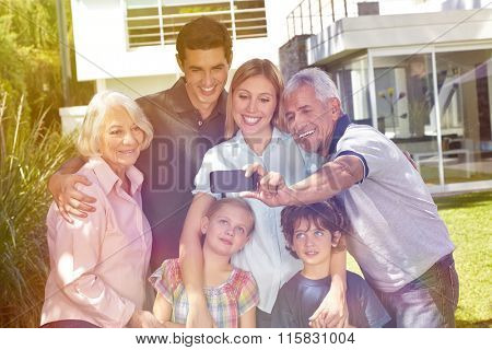 Grandfather taking selfie of a family with smartphone in a garden in summer