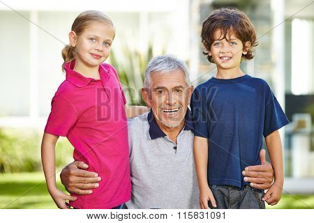 Portrait of smiling grandfather and two grandchildren in a garden