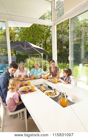 Family in three generations eating together at lunch table in summer