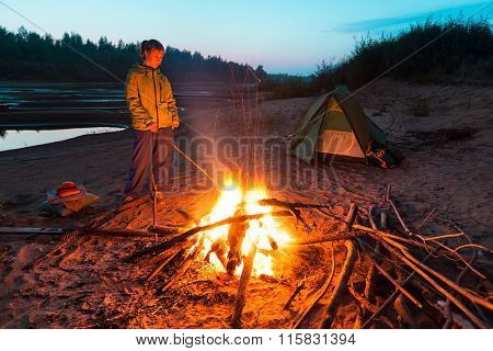 Lady standing by the bonfire and tent set in the wild area