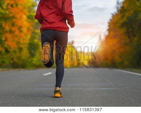 Lady running on the autumn asphalt road