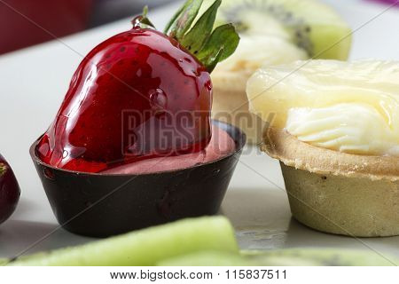 Variety of colorful mini tarts on plate.