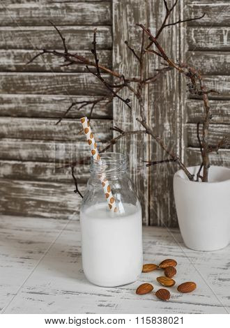 Almond Milk In A Glass Bottle And Almond On A Light Wooden Rustic Background