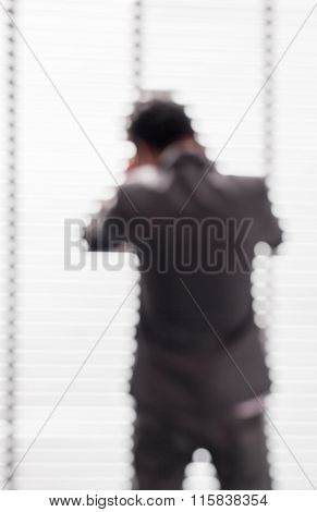 Blurred Picture Of Business Man Using Phone Near The Window In Office Building.