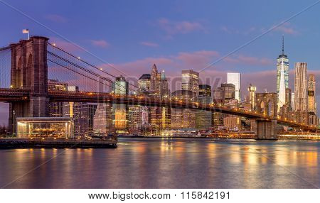 Brooklyn Bridge and Manhattan skyscrapers at sunrise time, beautiful gentle colors of sky and city illuminations, New York, USA