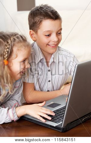 Children with laptop indoors. Happy kids playing computer at home.