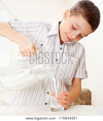 Child with glass pitcher milk. Boy drinking milk for breakfast