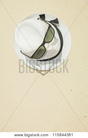white hat with black strap and black sunglasses placed on the beach