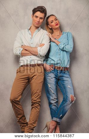 standing couple posing in studio background, man with hands crossed while woman with hand in pocket touch man's shoulder