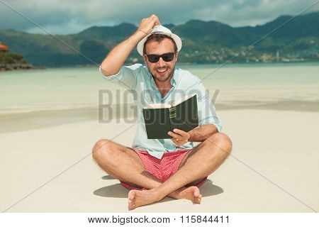 guy sitting on the beach and fixing his hat while reading a green book