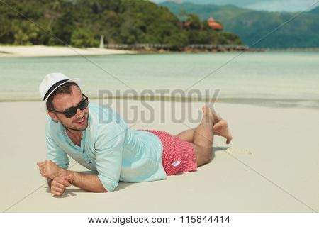 smiling man lying in the sand with his hands crossed while looking away from the camera