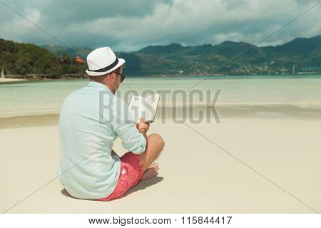 man in denim shirt reading a book on the beach while sitting with his hat on