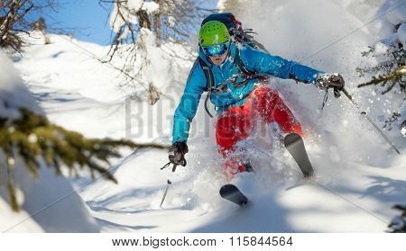 Man freerideer running downhill in forest