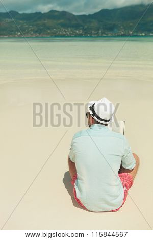 portrait from behind of a man sitting alone looking at the exotic beach in summer while reading a book
