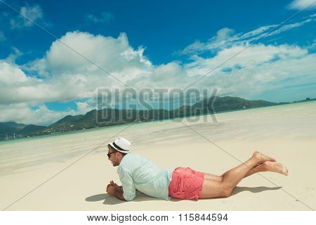 young man lying down in sand contemplating the exotic view