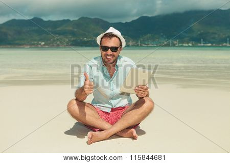 smiling guy sitting in the sand legs crossed with tablet in one hand and showing victory sign with the other one
