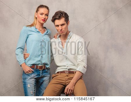 beautiful couple posing in studio background with him seated holding her while she stands hith hand in pocket