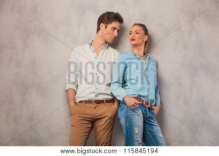 man standing with hands in pockets in studio background stares at woman while she pose looking away