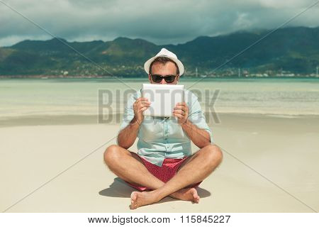 handsome man wearing sunglasses hiding behind tablet while sitting legs crossed on the beach