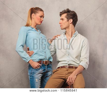 couple posing in studio, him looking at her while she holds her hand on his shoulder
