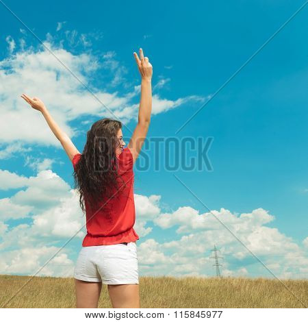 back view of a young girl with her hands in the air showing the victory sign while standing in the fields