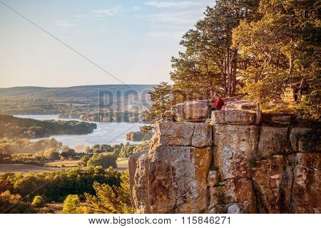 Man sitting on rock outcrop at Gibraltar Rock, Wisconsin.