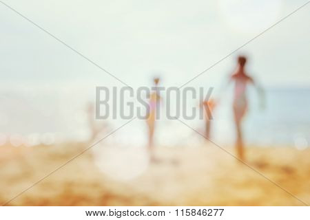 kids running at the beach, blurred background image.