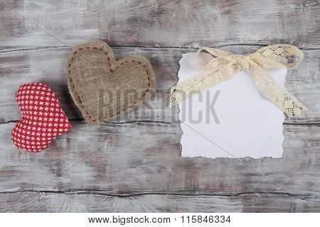 Two handmade hearts and white ragged paper sheet on wooden rustic background