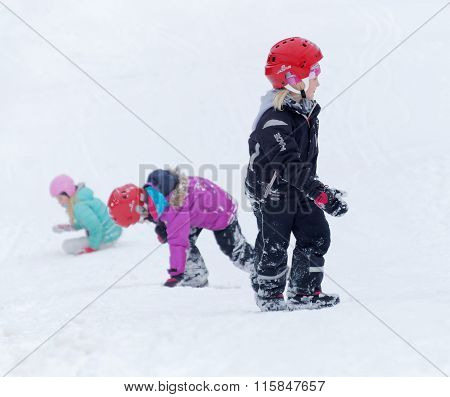 Three Kids Wearing Helmets Playing In A Snowy Slope