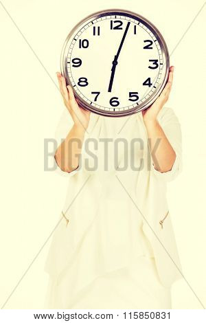 Businesswoman covering face with clock