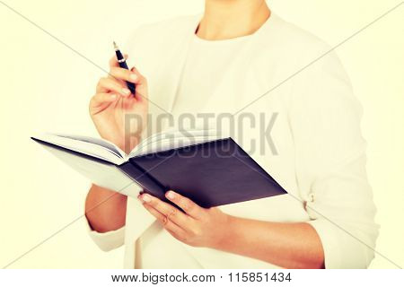 Young businesswoman thinks about some idea and makes a notes