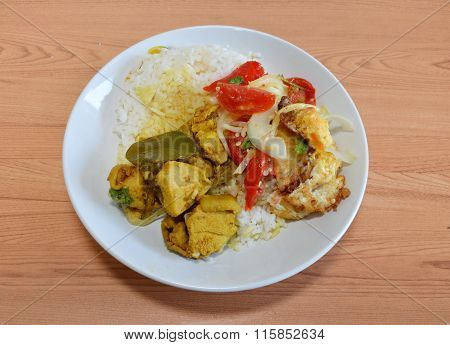 spicy salad with fried egg and chicken curry on rice