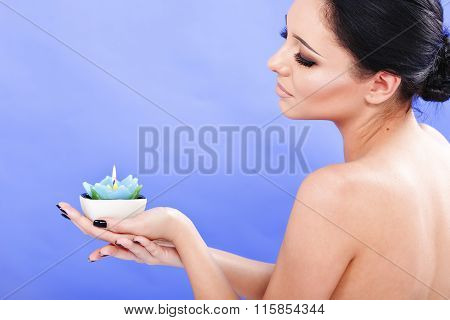 Beautiful Lady Relaxing With Candle In Spa