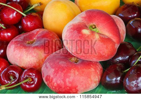 A tray full of fresh Saturn Peaches (flat Donut peach), apricots, wild and dark cherry