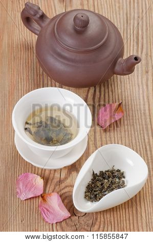 Green tea brewed in tea bowl and tea leaves served on rustic wooden table decorated rose petals