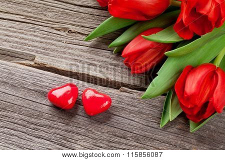 Red tulips and Valentines day candy hearts on wooden table