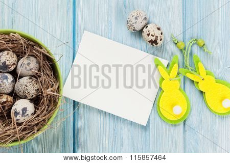 Easter greeting card with eggs in nest and decor over blue wooden table. Top view with copy space
