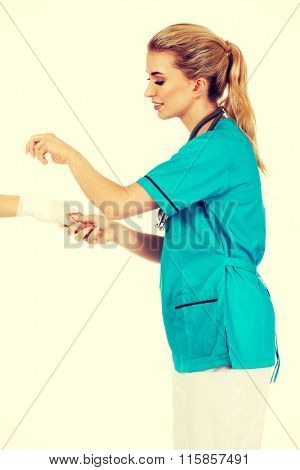 Young female doctor bandaging woman hand