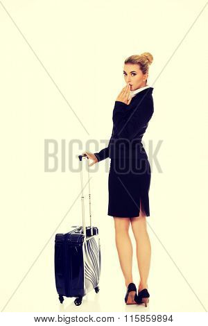 Surprised businesswoman with wheeled suitcase