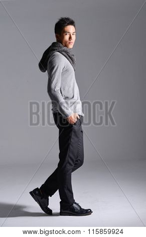 Full length portrait of young man with scarf walking in studio  Full length portrait of young man with scarf walking in studio