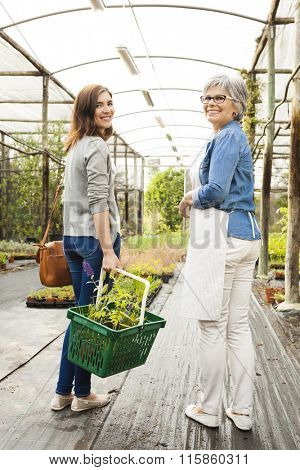 Florist and customer walking together in a greenhouse
