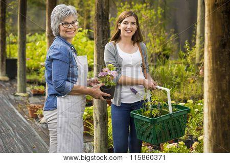 Beautiful mature florist helping a female customer to choose plants