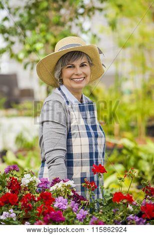 Beautiful mature woman gardening and looking at camera while smiling