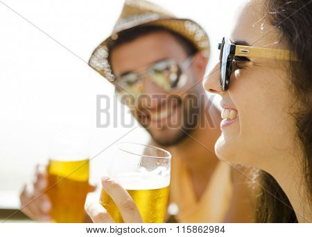Friends having fun and drinking a cold beer at the beach bar