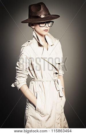 Fashion model posing at studio in a coat, hat and spectacles. Beauty, fashion. Business style.