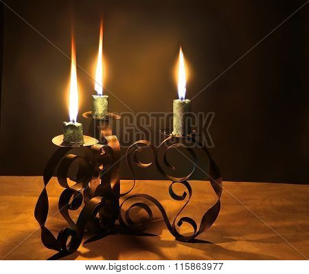 Three Burning Candles In A Candlestick